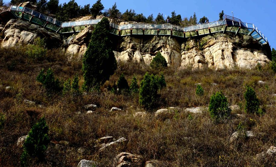 详情介绍 济南大石崮森林公园位于济南市市中区十六里河街道办事处石崮村,距市区仅有15公里。2009年底,在市中区农发局牵头下,成立了山东石崮寨都市农业生态园股份有限公司,加大了投资力度,大树、名贵树种大量进入园区,森林公园初具规模。今年,济南大石崮森林公园被批准为市级森林公园。古山寨文化是大石崮森林公园的最大特色:仿山寨大门、山腰古道盘绕、山上古寨屹立。截至目前,济南大石崮森林公园先后开发建设了蔬菜种植园、休闲木屋、鹿场、山寨景观等,复建了古驿站,修复了古驿道等,休闲观赏景点设施不断增多。  园区建有高